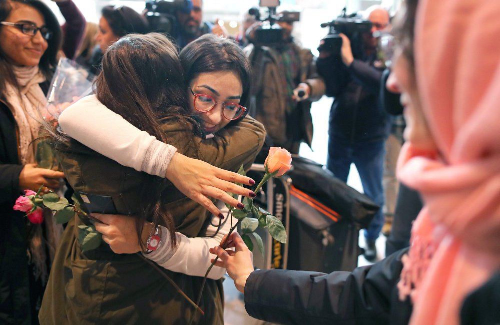Banah Al-Hanfy gets a hug and a rose after arriving at Logan International Airport on Friday. She met her parents and sisters after being delayed for a week by President Trump's executive order on immigration, which was stayed by a federal judge Friday night.