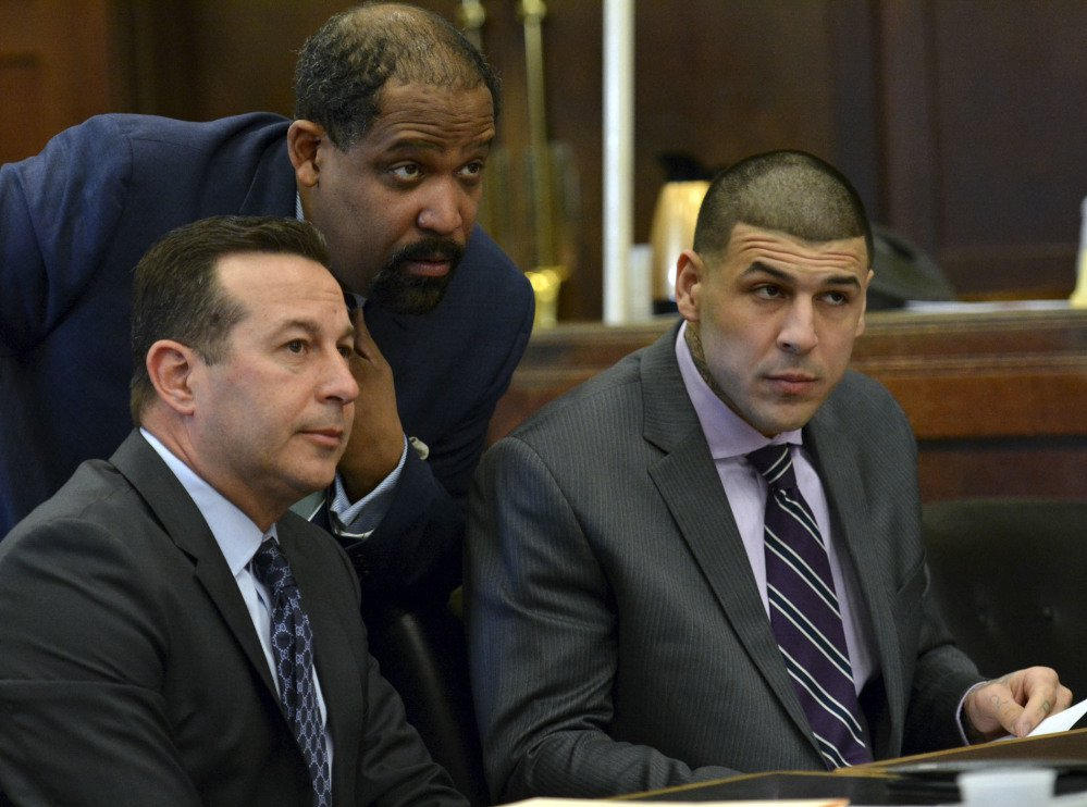 Lead defense attorney Jose Baez, from left, defense attorney Ronald Sullivan and Aaron Hernandez listen to Judge Jeffrey Locke during a hearing requesting a continuance Friday in Boston for Hernandez's upcoming double-murder trial.