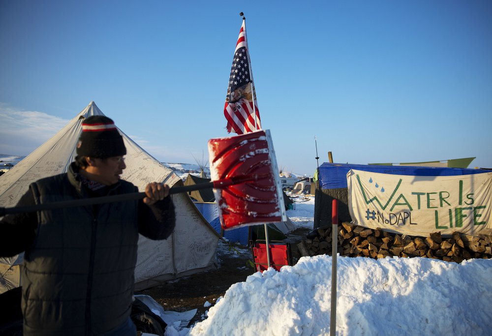 Benji Buffalo shovels snow at a camp in Cannon Ball, N.D., where people are protesting the Dakota Access Pipeline.