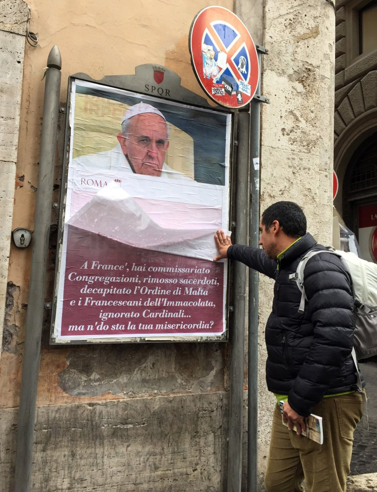 A passerby lifts a paper sheet covering an anti-Pope Francis poster to read it, in central Rome, Saturday, Feb. 4, 2017. On Saturday, posters appeared around Rome featuring a stern-looking Francis and questioning