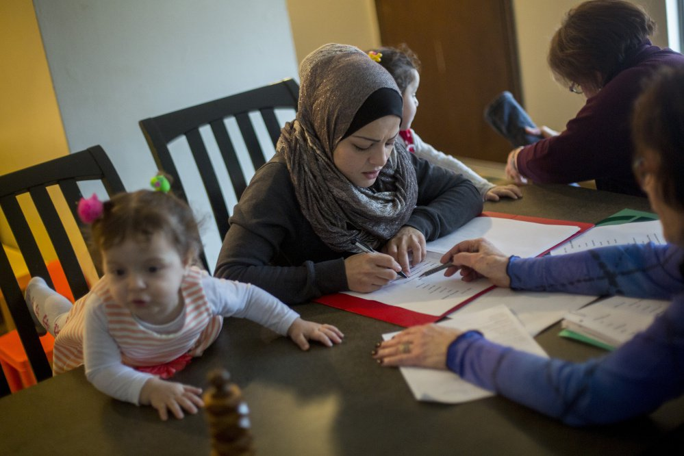Fatema Aljasem studies English as her children, from left, Ahed, 2, and Shahaad, 3, sit nearby at their apartment in Omaha, Neb., last week.