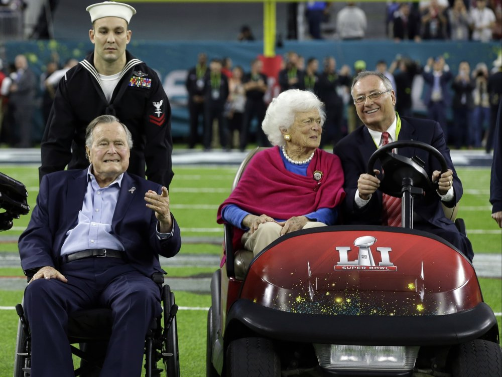 Former President George H.W. Bush and wife, Barbara, are escorted onto the field at NRG Stadium for the pregame coin toss before the Super Bowl in Houston on Sunday.