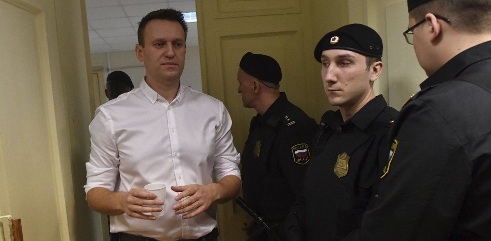Russian opposition leader Alexei Navalny, left, enters a courtroom for a retrial Wednesday in Kirov.
