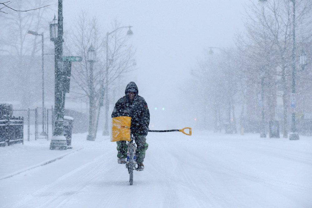 Angel Ares, of Hartford, bikes up Park Street on his way to shovel snow at buildings he takes care of in the Frog Hollow section of the city, as snow falls Thursday in Hartford, Conn.