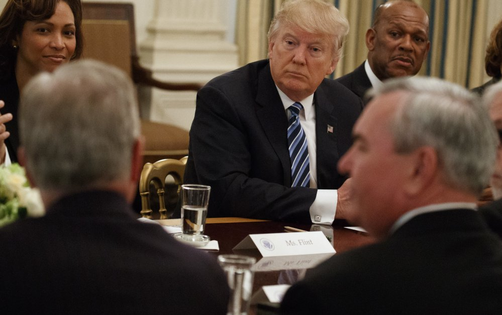 """President Trump listens Thursday during a meeting with airline and airport executives at the White House. Trump, who once ran his own airline, pledged to help the companies deliver """"the greatest service"""" with minimum delays and at the lowest cost in modernized facilities."""