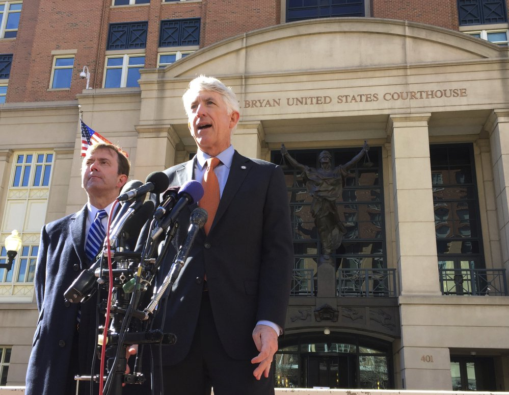 Virginia Attorney General Mark Herring, right, accompanied by Virginia Solicitor General Stuart Raphael, speaks outside the federal courthouse in Alexandria, Va., on Friday following a hearing on President Trump's travel ban.