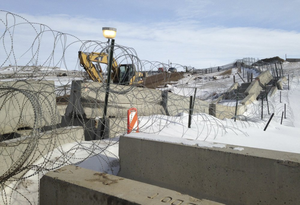 Razor wire and concrete barriers protect access to the Dakota Access pipeline drilling site Thursday near Cannon Ball, North Dakota. The developer says construction of the Dakota Access pipeline under a North Dakota reservoir has begun and that the full pipeline should be operational within three months.