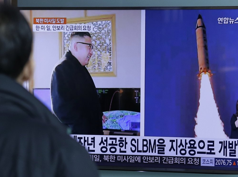"A man at Seoul Railway Station watches a program showing photos published in North Korea of the ""Pukguksong-2"" missile launch and North Korean leader Kim Jong Un."