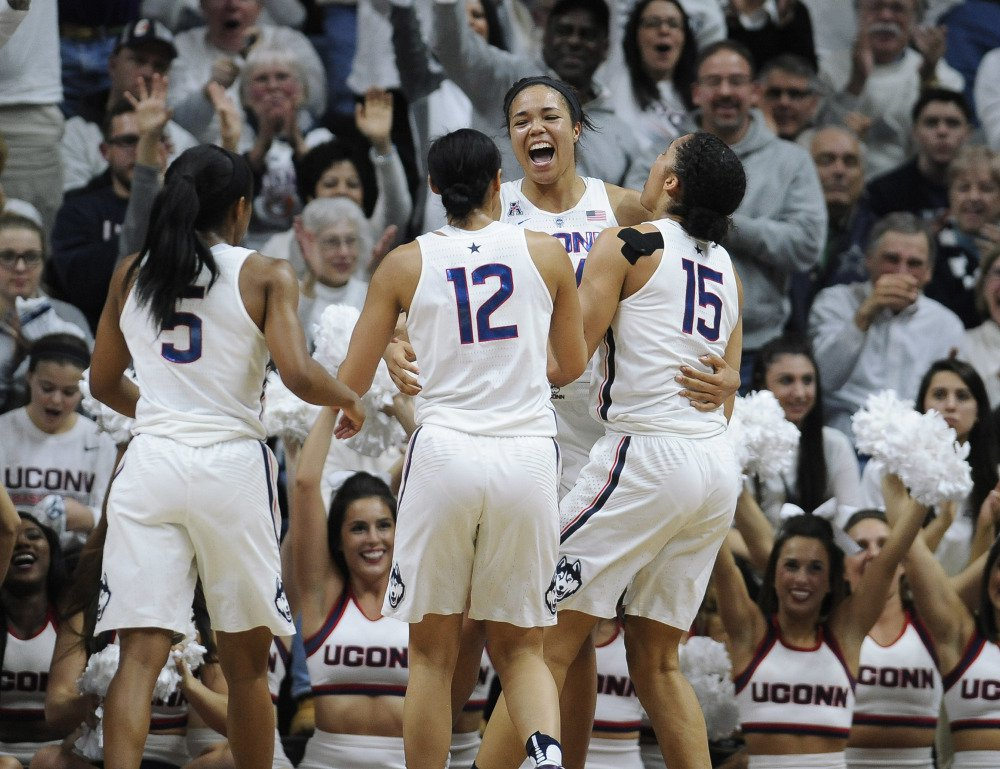 Connecticut's Napheesa Collier, center, reacts with teammates Crystal Dangerfield, left, Saniya Chong and Gabby Williams, right, in the second half of Monday night's game against South Carolina, the 100th consecutive win for the Huskies.