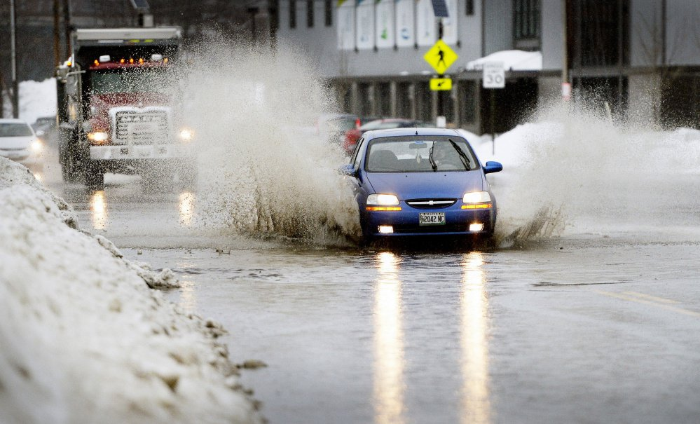 A motorist navigates a flooded stretch of Commercial Street in Portland on Wednesday as the city gets doused.