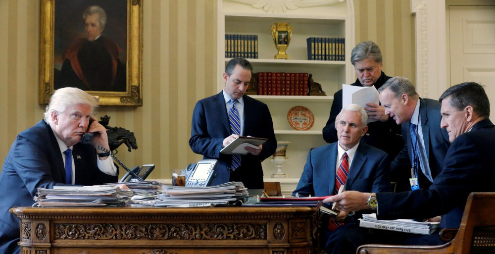 President Trump, joined by, from left, Chief of Staff Reince Priebus, Vice President Mike Pence, senior adviser Steve Bannon, Communications Director Sean Spicer and national security adviser Michael Flynn, works in the Oval Office on Jan. 28.