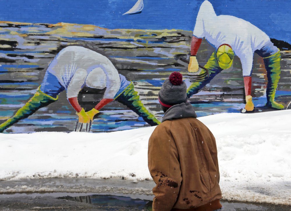 Two linf seeyse sdf fs yPORTLAND, ME - FEBRUARY 16: Clammers appear to be digging in snowpiles in artist Susan Bartlett Rice's mural as Larry Mundu, of Portland, walks past. (/Staff Photographer) Top photo A stop sign in Kennebunk is coated in wet snow on Thursday morning, February 16, 2016. Stop is what many Mainers may be thinking this morning as they wake up to another day of digging themselves out from more snow that fell overnight. (Staff Photo by Gregory Rec/Staff Photographer)