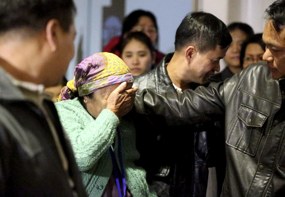 Thang Dim, left, a refugee from Myanmar, wipes away tears as her son Zam Piang, right, comforts her at Tulsa International Airport in Tulsa, Okla., on Tuesday. The first group of refugees arrived in Tulsa since a federal judge blocked President Trump's travel ban on refugees.