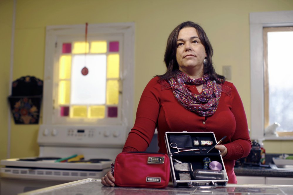 """In the kitchen of her Hollis home, legalization supporter Heather Sullivan, 45, the mother of a 7-year-old, shows the locked cases where she keeps her paraphernalia. """"I am not going to sit next to my son on the couch and roll a joint,"""" she said, but """"I might slip into the basement after a long day, though."""""""