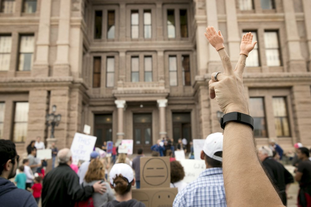 "Peter Costa of Windham, N.H., gestures at Monday's ""Not My President"" rally in Austin, Texas. Protests were held across the country, but crowds were smaller than seen at President Trump's inauguration. Police arrested some unruly protesters in Oregon."