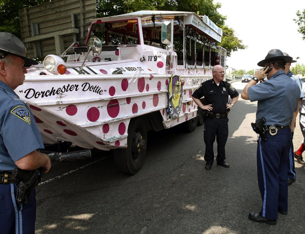 Boston police officers work the site of a crash involving an amphibious duck boat in June 2010 that left some passengers with minor injuries. New safety regulations are set to go into effect in April after a duck boat ran over and killed a 28-year-old woman last spring.