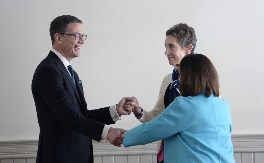 """The University of New England's next president, Dr. James Herbert, greets presidential search committee Chairwoman Gloria Pinza and current UNE President Danielle Ripich after Tuesday's news conference in Portland. """"James is a delightful person who has demonstrated a tremendous work ethic, a warm and engaging personality and a good sense of humor,"""" Pinza said."""
