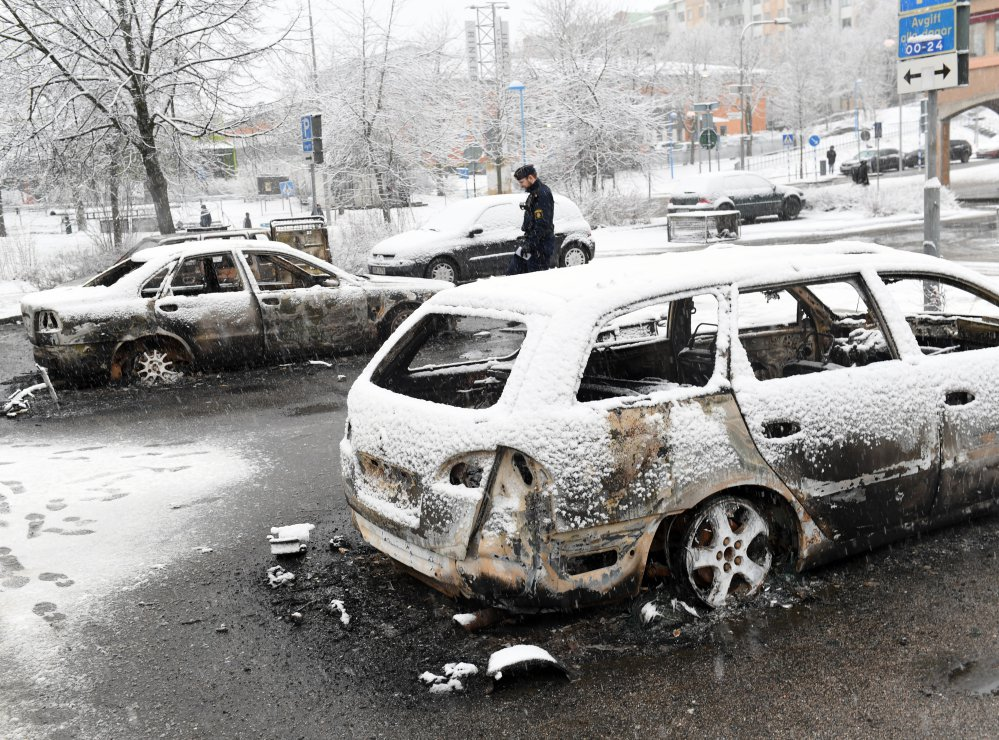 A police officer investigates a burned out car in Rinkeby, outside Stockholm, on Monday. While the country has some friction, it's hardly an extremist breeding ground.