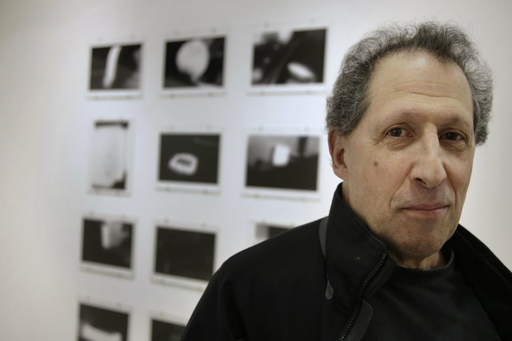 "Photographer Karl Baden of Cambridge, Mass., stands in front of an exhibit of his photographs from 1976 called ""Thermographs,"" at the Miller Yezerski Gallery in Boston."