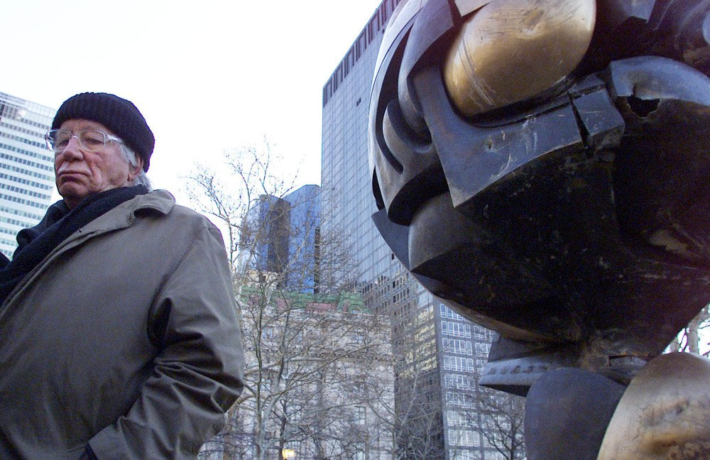 "German artist Fritz Koenig stands next to his bronze sculpture ""The Sphere"" after a re-dedication ceremony in New York in 2002. Koenig, whose sculpture became a symbol of resilience after the Sept. 11 attacks in New York, died Wednesday at the afe of 92."
