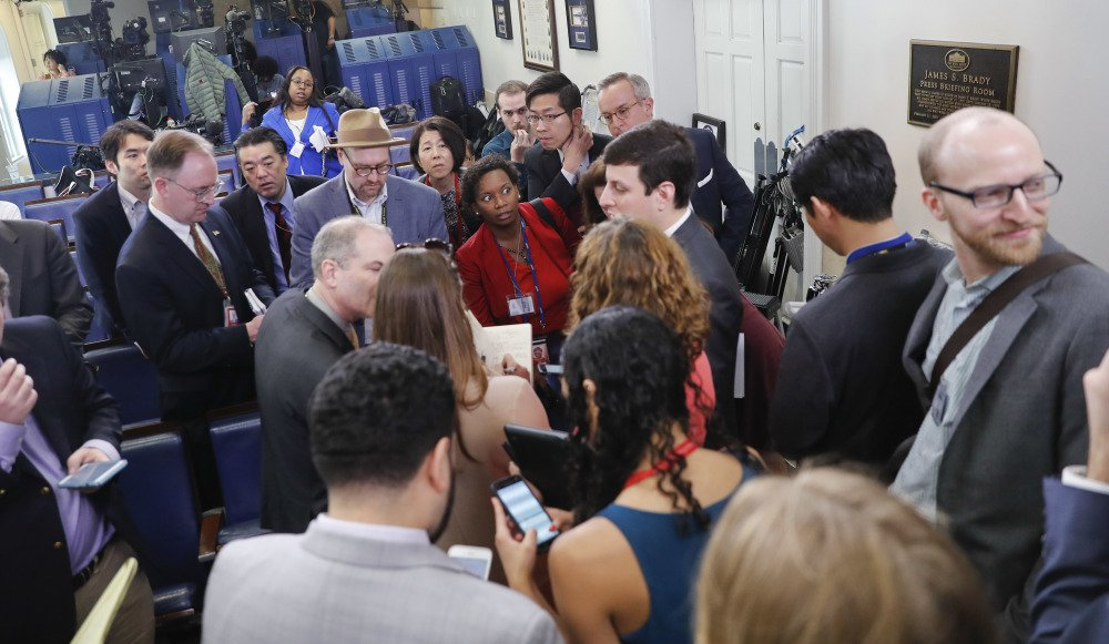 Reporters line up in hopes of attending a briefing in press secretary Sean Spicer's office at the White House in Washington on Friday. The White House held an off-camera briefing in Spicer's office, where they selected who could attend.