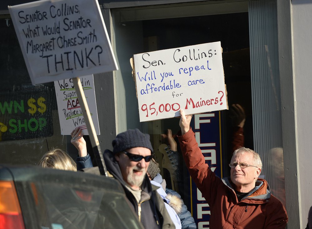 Henry Ingwersen, right, of Arundel holds a sign questioning Sen. Susan Collins' stance on Obamacare during the Biddeford demonstration last week. Though she eschews town-hall style gatherings, the senator says she held more than a dozen meetings and interviews with media and her constituents.