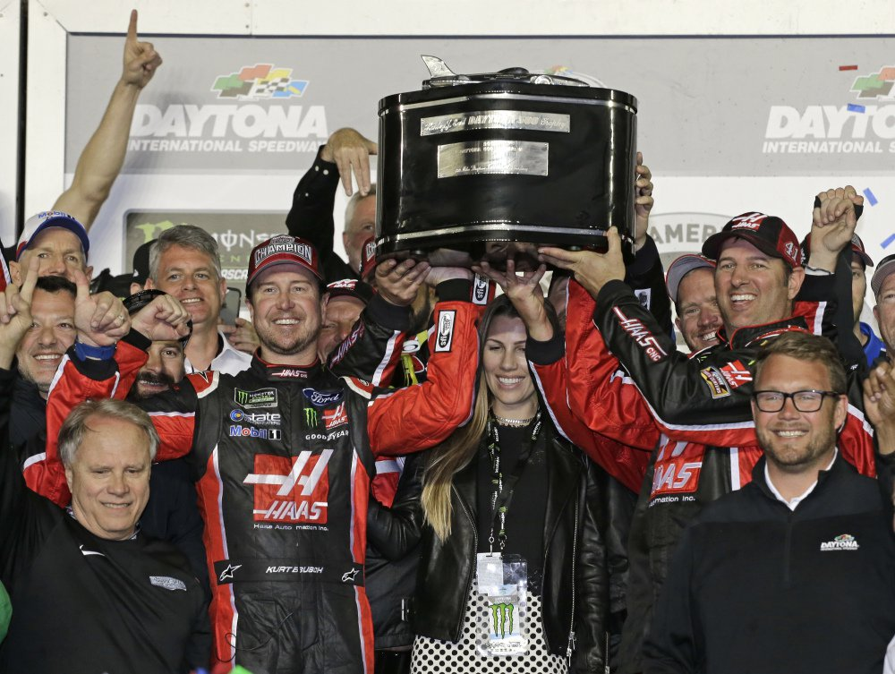 Kurt Busch, center left, and team members raise the trophy after Busch won the Daytona 500 Sunday at Daytona International Speedway in Daytona Beach, Fla.
