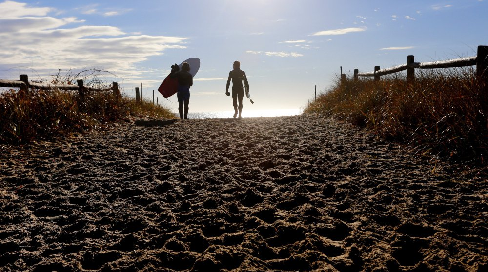Surfing buddies Stephan Laufer of Germany, left, and Ryan McDermott of Scarborough head toward the water to take advantage of waves at Scarborough Beach State Park. Maine oversees more than 50 state parks and historic sites.