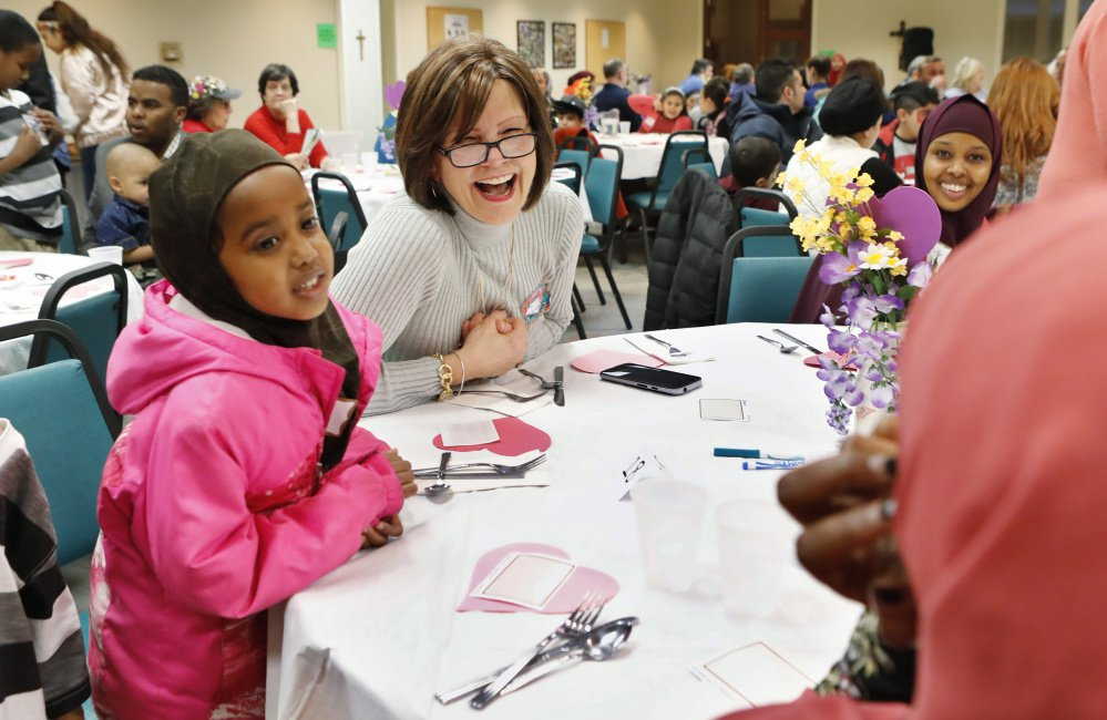 "Kelly Dell'Aquila, center, Habso Ali, 8, left, and others interact during the Building Bridges dinner at Saint Maximilian Kolbe church in Scarborough. ""We need more of this,"" said Zoe Sahloul of Westbrook. ""Whenever we have the chance, we need to come together."""