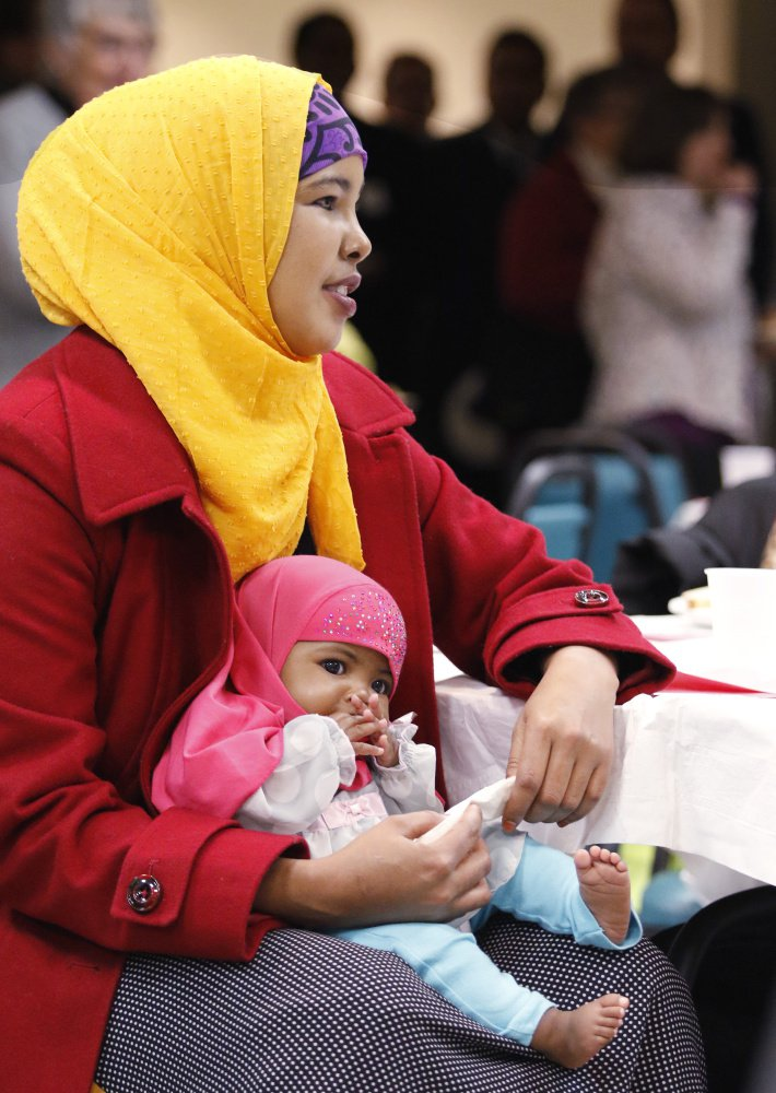 Hosna Sheikn of Lewiston holds her 3-month-old daughter, Ibtisam Afrah, during the dinner. Participants of all ages included refugees and other immigrants from Iraq, Lebanon, Somalia and the Democratic Republic of the Congo.