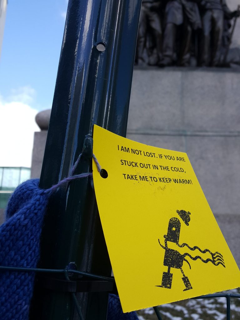A hat sits attached to a fence in Monument Square on Friday with a note that encourages those in need to take the hat.   James Patrick/Staff Photo