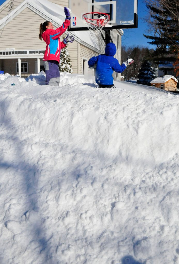 Standing on a 6-foot-tall snowbank, Avery Willett, left, and her brother, Hunter, slam dunk snowballs in a basketball hoop at their home in Waterville on Tuesday. The kids had the day off from school because of the latest winter storm.