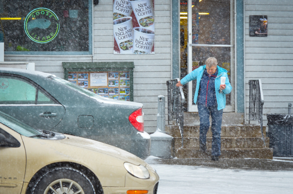 A woman carefully navigates the steps Wednesday at Christy's Market in Belgrade after stopping for a cup of coffee. Snow during Wednesday's morning commute made some roads slick, leading to accidents around the area.