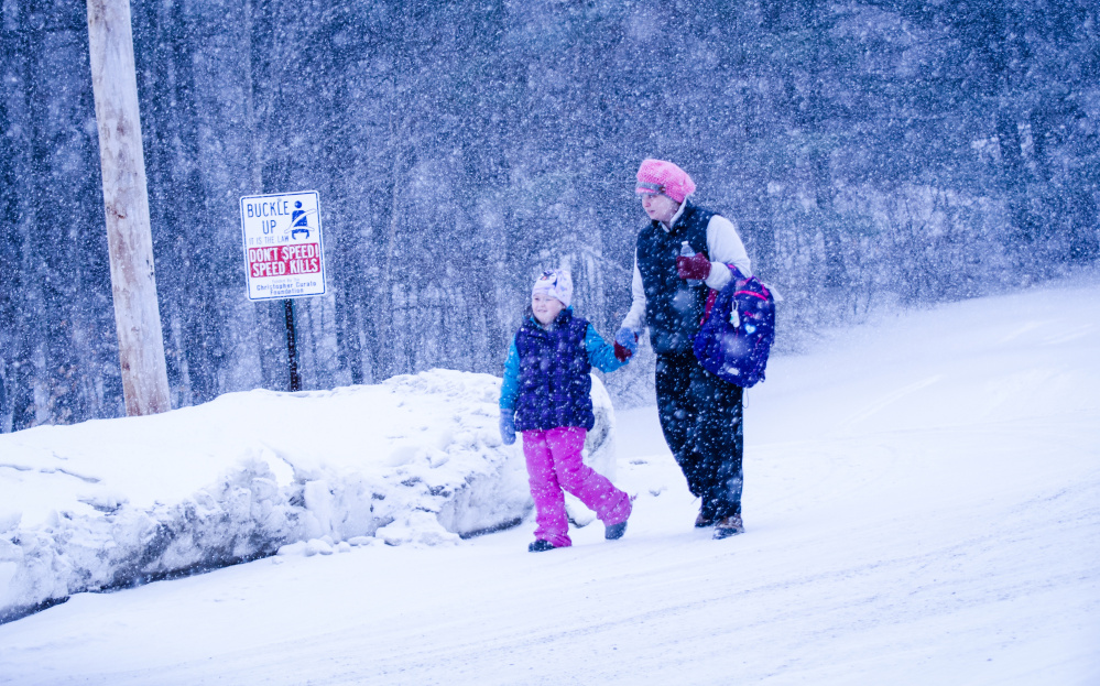 Flurries greet this parent and child Wednesday morning as they walk to Belgrade Middle School on Depot Road in Belgrade.