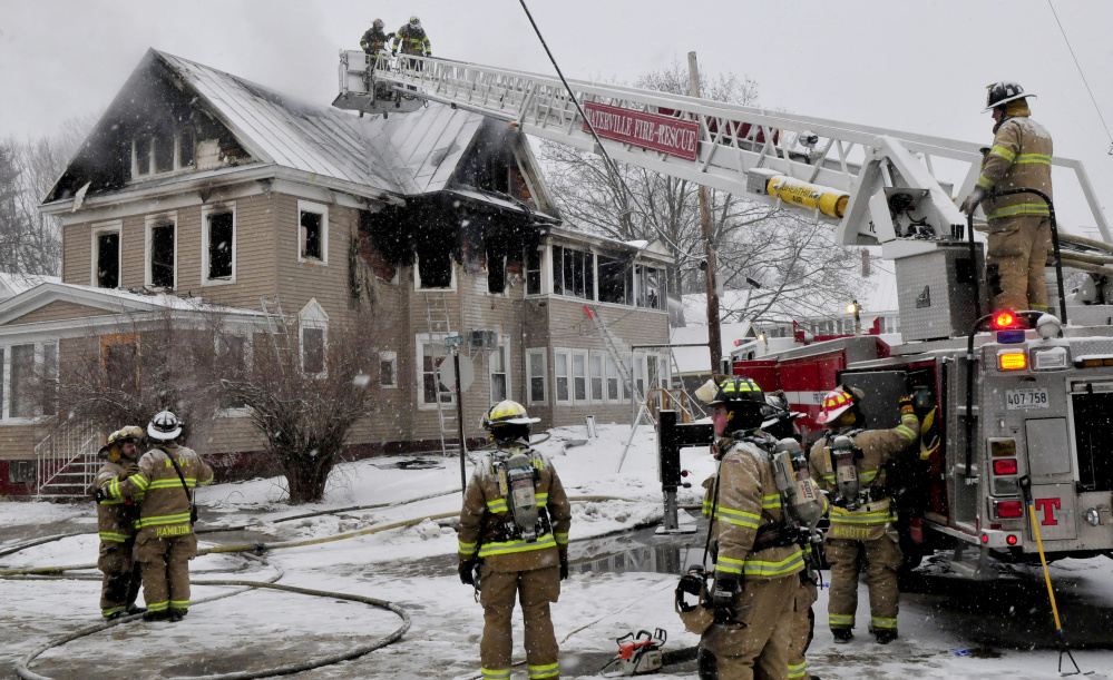 Firefighters continue working Wednesday at the scene of a fire that severely damaged an apartment building in the morning on Summer Street in Waterville.