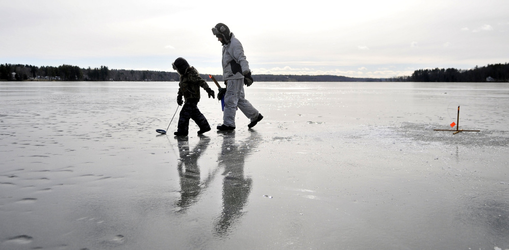 Kyle Willette, and his son Brody, 5, set the lines during a session of ice fishing on China lake near Causeway Road in China Friday. Willette noted the wind was not as bad as the past couple of days making Friday a perfect day on the ice.