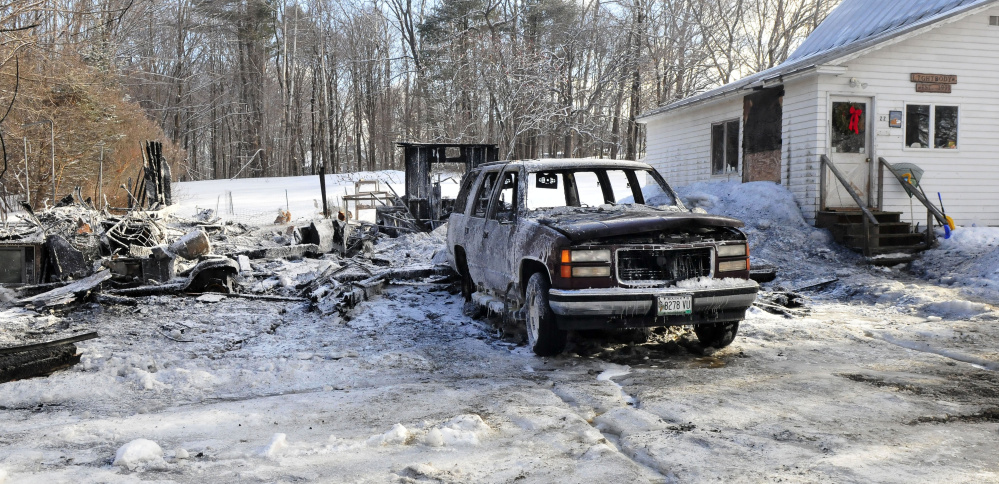 Charred remains lie on the spot Thursday where a garage stood until it and its contents, as well as the Chevrolet Suburban in the foreground, burned Wednesday night at a home on Young Street in Madison.
