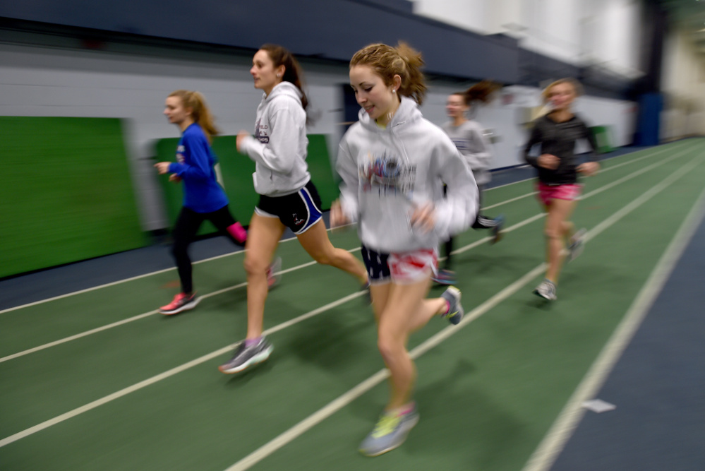 Messalonskee High School middle distance runner Avery Brennan, foreground, warms up with teammates for practice Wednesday at Colby College.