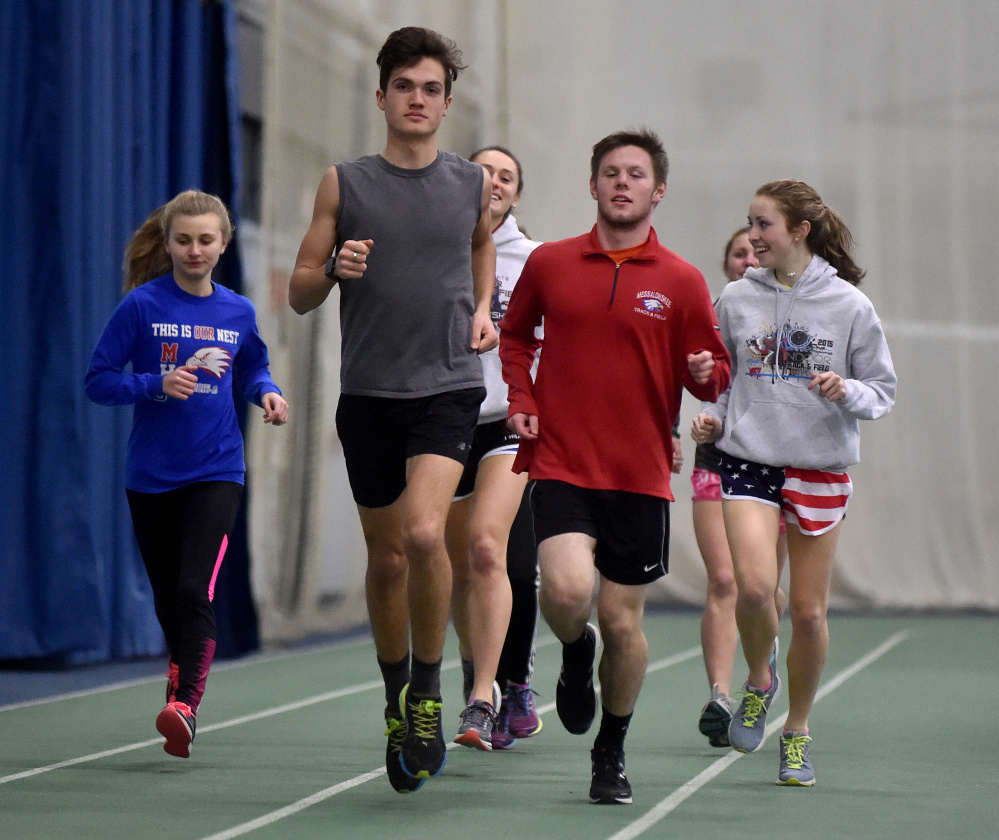 Messalonskee High School middle distance runners, Zach Hoyle, front center, Dan Turner, right center, and Avery Brennan, back right, warm up for practice at the Colby College field house earlier this week.