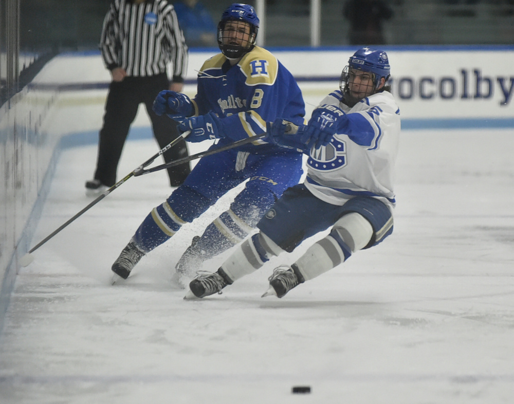 Hamilton's Xavier Morin, left, battles for the puck with Colby's Dan Dupont during the first period Friday in Waterville.