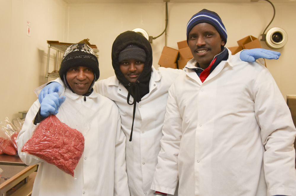 Central Maine Meats employees, from left, Hassan Aweig, Mohamud Aden, and Muhamed Mussa assist in processing meat according to halal standards. The employees are Muslim and immigrated to Gardiner from Somalia.