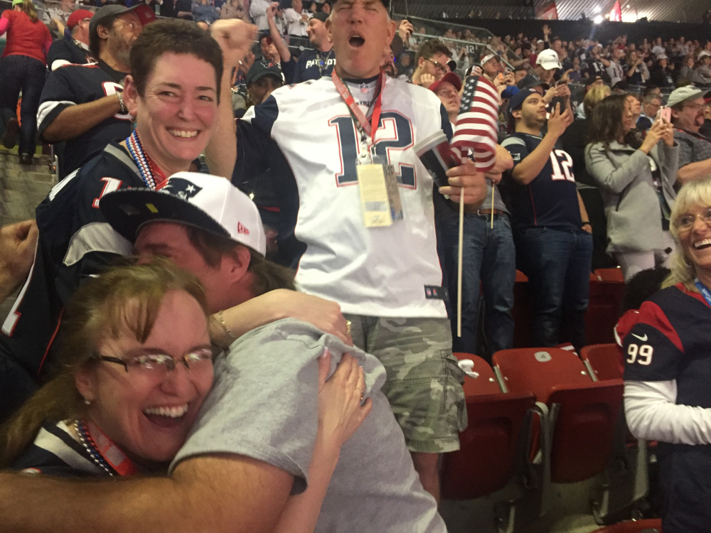 West Gardiner natives Cindy Smith, left, receives a hug from her brother Tim Greenleaf as fellow Patriot fans celebrate during Super Bowl 51 on Sunday night.