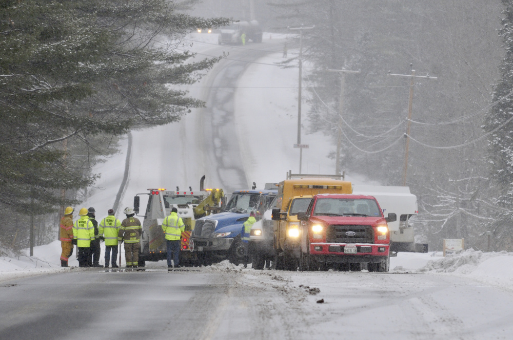 Wayne and Readfield firefighters, along with the Maine State Police, the Maine Department of Transportation and the Maine Department of Environmental Protection, work on Tuesday at the scene where an oil truck that overturned is being flipped back onto its wheels on Route 133 in Wayne.
