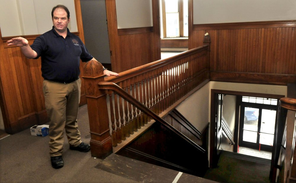 Travis Works, executive director of the Cornville Regional Charter School, points out the ornate woodwork, including the stairwell, in the former Variety Drug building in Skowhegan. The school is buying the property and will renovate the building into offices and rooms for classes.