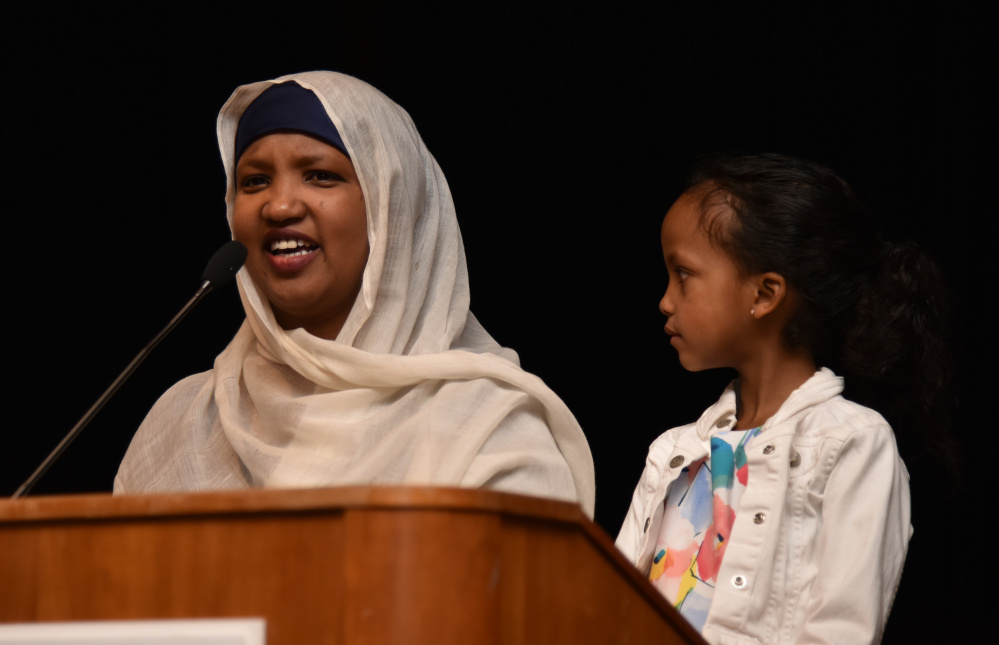Fatuma Hussein, the founder and executive director of the Immigrant Resources Center of Maine, speaks on Wednesday night at a forum held at the University of Maine at Augusta in response to Ku Kllux Klan fliers placed around  Augusta and other locations in the state. Her daughter listens as Hussein talks about what it was like to move to Lewiston from Somalia.