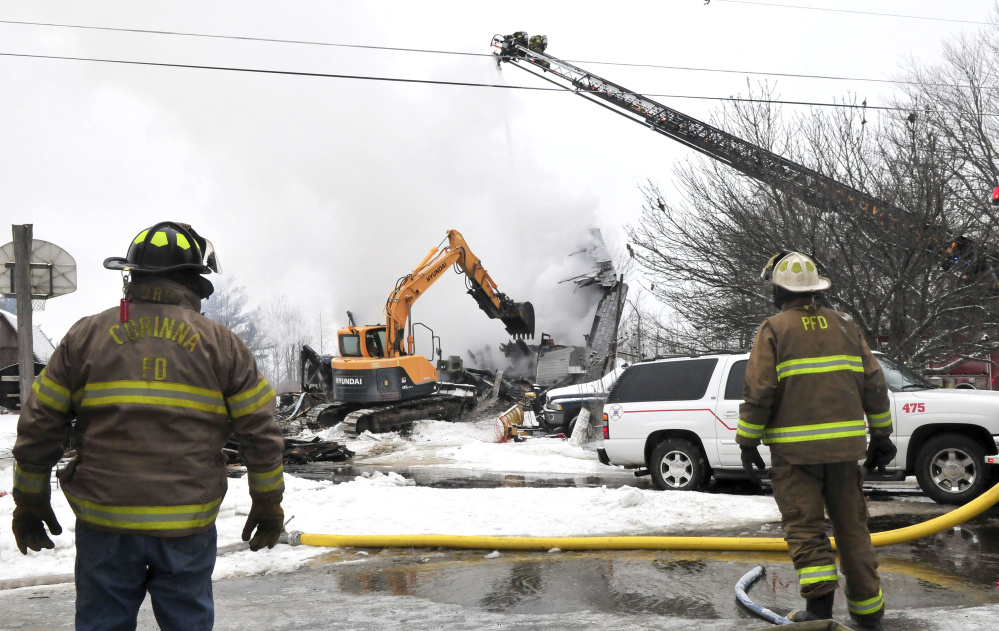 Firefighters from the Skowhegan Fire Department spray water from a ladder truck as an excavator tears down an apartment building on Square Road in Palmyra that was destroyed by fire Tuesday. Two people — Kayla Brown and Roger Brown — apparently were killed in the fire.