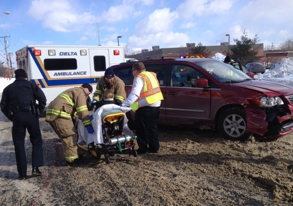 Melissa Finley, of China, is taken by stretcher to a waiting ambulance after a car crash Friday morning on College Avenue in Waterville.