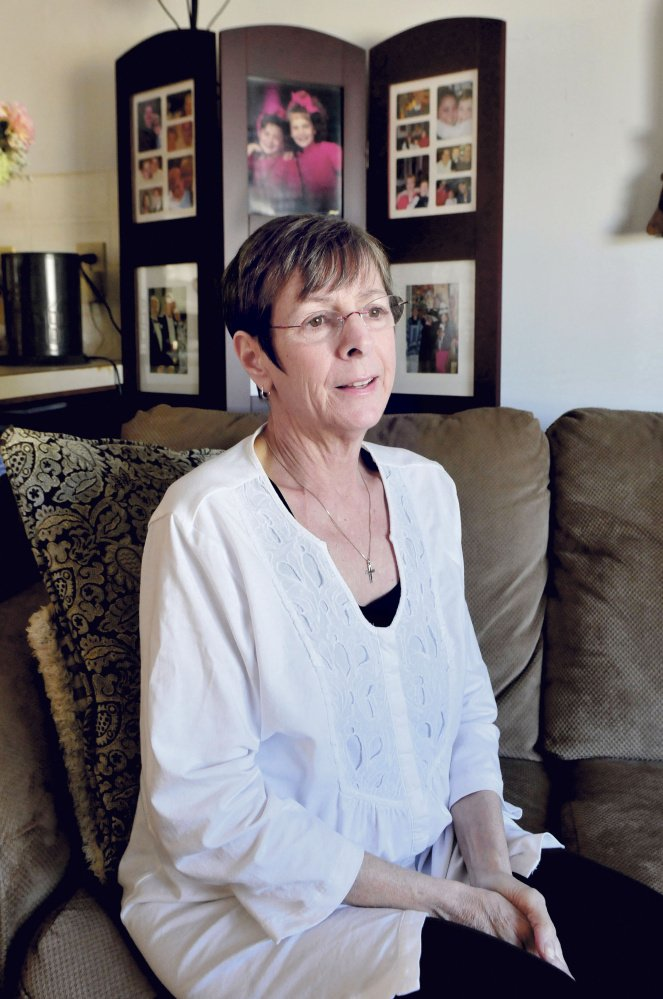 Rebecca Kane, beside a photo album of her family in Waterville on Monday, talks about dealing with cancer and how doctors have told her she has a year or less to live. Kane said her religious faith and support from family and friends sustain her.