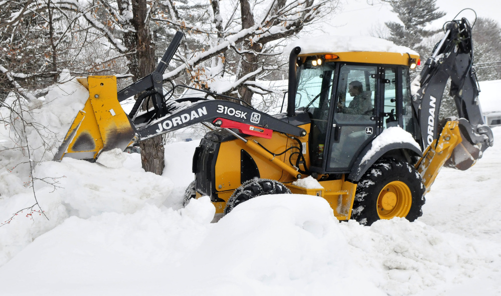 Jared Clukey of the Jordan Lumber company uses a bucket loader to pile up snow at a residence in Kingfield on Sunday to make room for the forecast 2 feet of snow expected to fall through Tuesday.