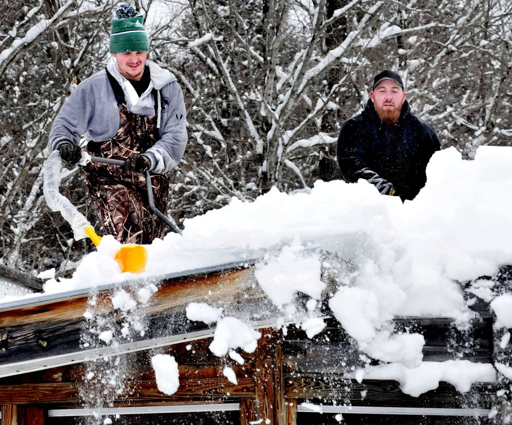 """Jake Boivin, left, and Chad Merrill use snow scoops to clear deep snow from a rooftop in New Vineyard on Sunday.  """"With 2 feet of snow coming tomorrow, I figured I better shovel this off,"""" Merrill said."""